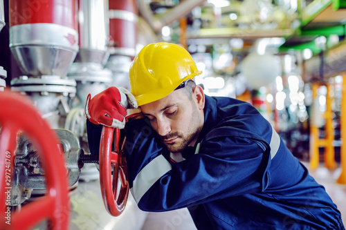 Pinturas sobre lienzo  Hardworking caucasian worker in working clothes leaning on big valve and sleeping