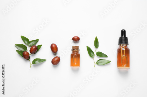 Glass bottles with jojoba oil and seeds on white background, top view Fototapet