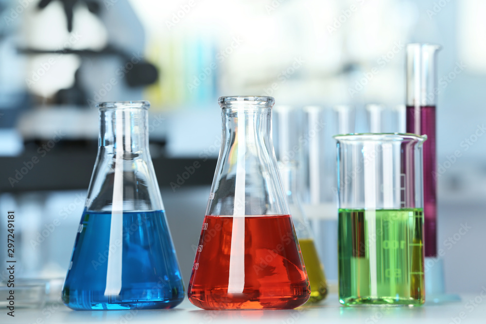 Fototapety, obrazy: Glassware with colorful liquids on table in laboratory