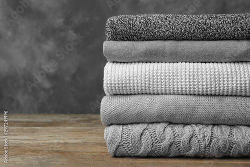 Fotografía  Stack of warm clothes on wooden table against grey background