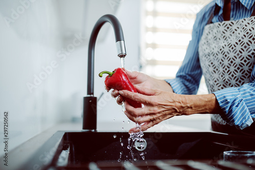 Pinturas sobre lienzo  Close up of caucasian senior woman in apron washing red pepper in kitchen sink