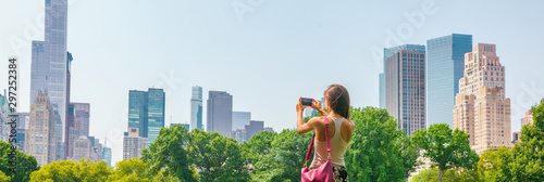 New York City tourist taking photo with phone of NYC Skyline of skyscrapers buildings towers in summer travel vacation panoramic banner background.