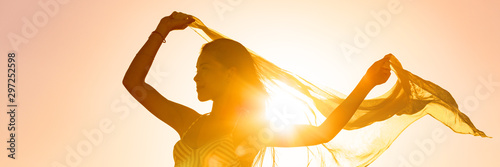 Fotografie, Obraz  Beautiful woman happy free in sunset glow waving scarf in the wind dancing in sun panoramic banner