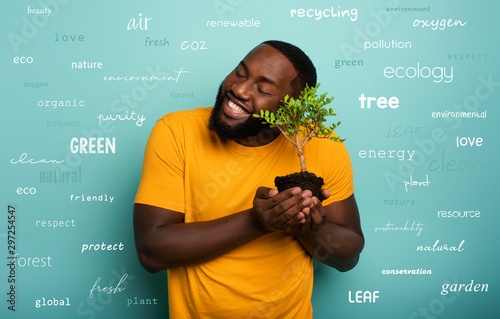 Photo Happy boy hugs a small tree ready to be planted over a light blue color