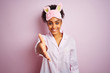 Young african american woman wearing pajama and mask over isolated pink background smiling friendly offering handshake as greeting and welcoming. Successful business.