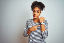African American Woman Wearing Navy Striped T-shirt Standing Over Isolated White Background In Hurry Pointing To Watch Time, Impatience, Looking At The Camera With Relaxed Expression