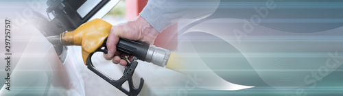 Fotomural  Hand holding fuel pump nozzle and refilling car; panoramic banner
