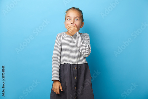 Vászonkép Funny little girl covers mouth with surprise, has a shocking expression on face, emotional portrait on blue isolated