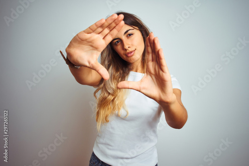 Fototapeta Young beautiful woman wearing casual white t-shirt over isolated background doing frame using hands palms and fingers, camera perspective obraz