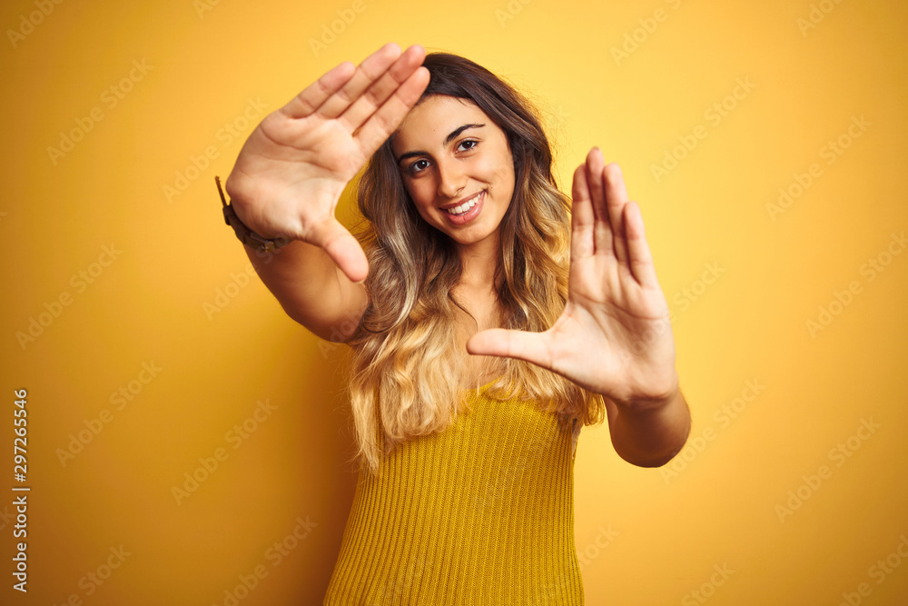 Fototapeta Young beautiful woman wearing t-shirt over yellow isolated background doing frame using hands palms and fingers, camera perspective