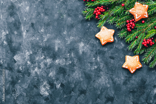 Nature Christmas and New Year background with winter berries, ginger cookies in the form of a star and fir branches in a dark style. Copy space and top view.