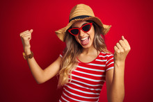 Young Beautiful Woman Wearing Sunglasses And Summer Hat Over Red Isolated Background Very Happy And Excited Doing Winner Gesture With Arms Raised, Smiling And Screaming For Success