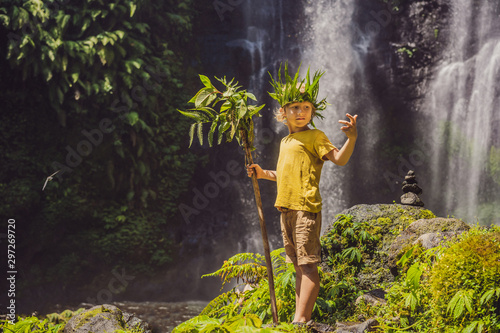 Fotografia Cute boy depicts the king of the jungle against the backdrop of a waterfall