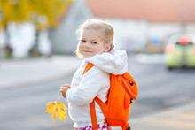 Cute Little Adorable Toddler Girl On Her First Day Going To Playschool. Healthy Happy Baby Walking To Nursery School. Child With Backpack Going To Day Care On The City Street, Outdoors