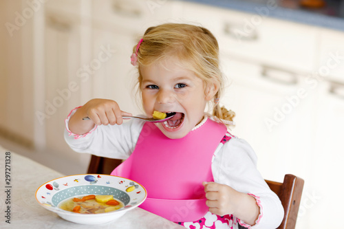Fotografija Adorable toddler girl eating healthy vegetable meal with potatoes and carrots soup for lunch