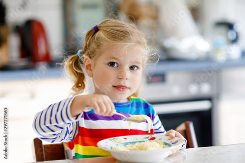 Fototapeta Adorable toddler girl eating healthy chicken noodle soup for lunch. Cute happy baby child taking food at home or nursery daycare or kindergarten and learning using spoon. obraz