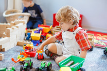 Little Cute Toddler Boy Playing With Car And Tractor Toys. Happy Baby Child Playing At Playschool Or Kindergarten. Children At Day Care Doing Activity