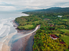 Aerial View Of Black Sand Beach With River, Ocean And Waves In Bali