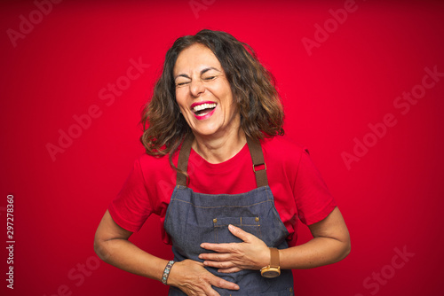 Obraz na płótnie Middle age senior woman wearing apron uniform over red isolated background smiling and laughing hard out loud because funny crazy joke with hands on body