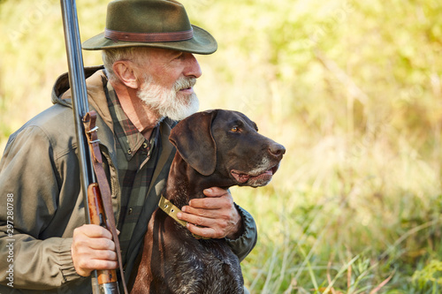 Photo Caucasian mature man with gun and dog sit searching prey