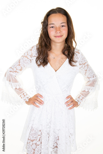 Smiling dark-haired dressed young woman in white girl dress stands on white back Slika na platnu