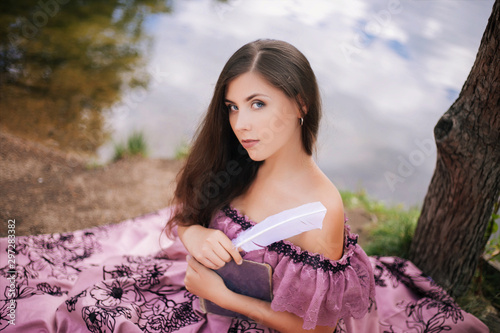 Cuadros en Lienzo A beautiful young woman in a 19th-century dress sits by a pond and writes with a quill pen in a book, a portrait