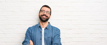 Handsome Man With Beard Over White Brick Wall With Glasses And Happy
