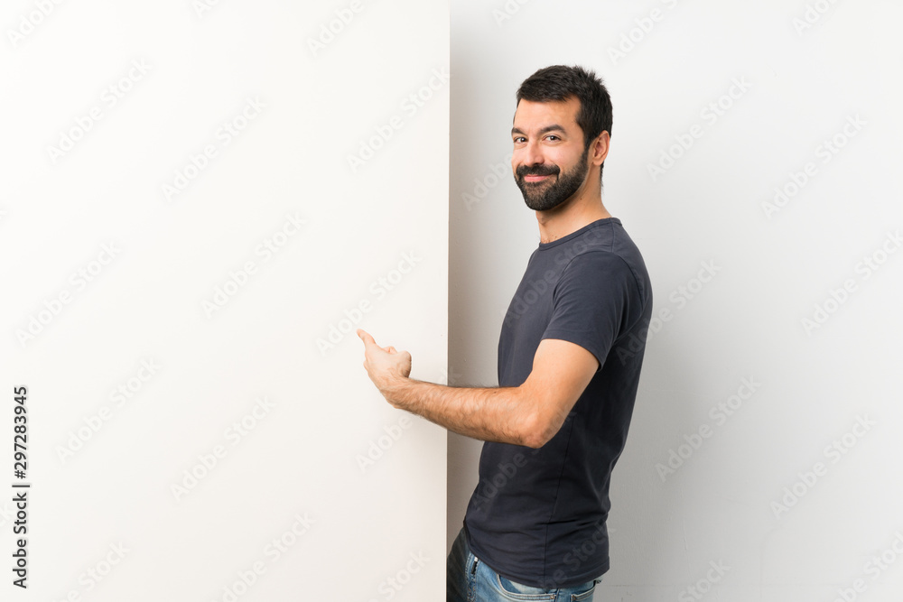 Fototapeta Young handsome man with beard holding a big empty placard pointing back