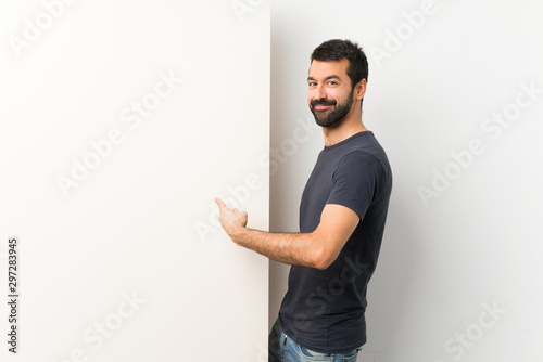 Young handsome man with beard holding a big empty placard pointing back - 297283945