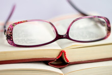 Against The Background Of Opened Books With Verses Are Women's Glasses For Sight