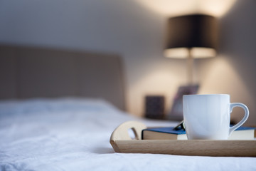Cup of hot drink and book on bed