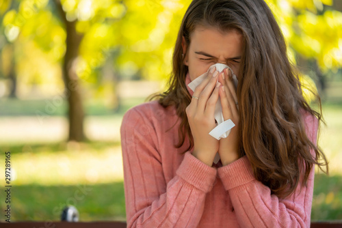 Fototapeta Young woman with allergy sneezing and blowing her nose in a handkerchief tisue, outdoor in a park. obraz