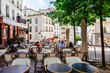Leinwanddruck Bild - Cozy street with tables of cafe in quarter Montmartre in Paris, France