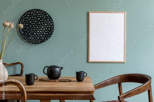 Fotomural  Stylish scandinavian dining room interior with mock up poster frame, wooden table, furniture, teapot with cups, black decoration and elegant accessories
