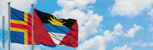 Fotomural Aland Islands and Antigua and Barbuda flag waving in the wind against white cloudy blue sky together