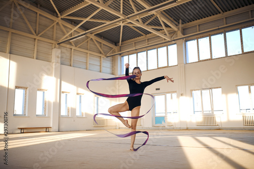 Garden Poster Fitness Active beautiful rhythmic gymnast standing in Sur le cou-de-pied pose, waving long colourful ribbon in the air, dancing in bright sports hall, professional sport concept
