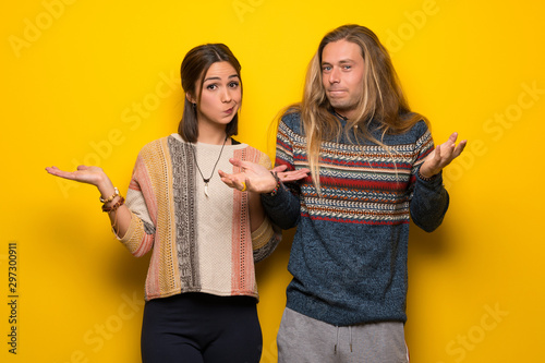 Obraz na plátně  Hippie couple over yellow background having doubts while raising hands and shoul
