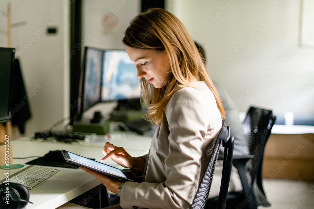 Fototapety, obrazy: Young woman working in her office
