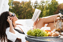 Image Of Beautiful Young Woman Drinking Coffee And Reading Book On Terrace