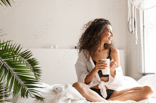 Fototapeta Image of beautiful young woman drinking tea on bed in white apartment