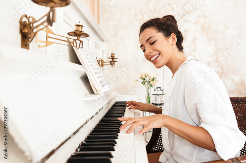 Lady in white shirt play the piano indoors at home. Fotobehang