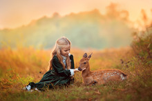 A Cute Little Blonde Girl In A Green Vintage Dress Sits Next To A Small Sika Deer Around Them Yellow Beautiful Autumn Trees.