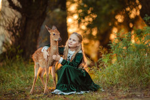 A Beautiful Blonde Girl In A Green Vintage Dress Stands Next To A Sika Deer In The Forest At Sunset.