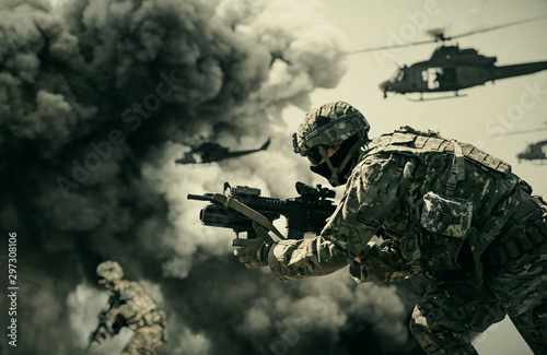 Obraz Military helicopter and forces between fire and dust in the battlefield - fototapety do salonu