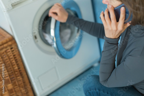 A woman calls a repair service for a breakdown of a washing machine Fototapet