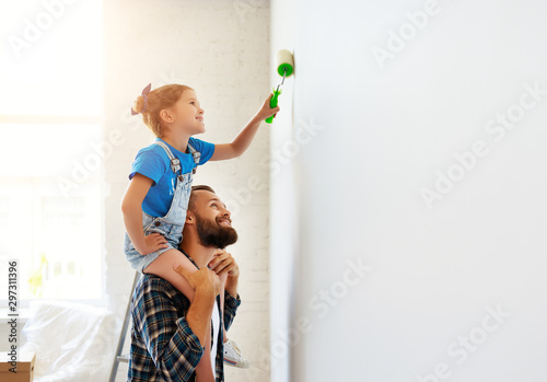 Obraz Repair in apartment. Happy family father and child daughter paints wall - fototapety do salonu