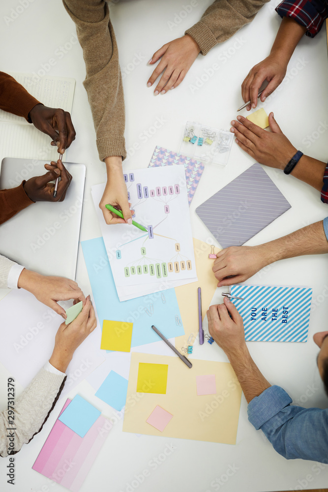 Fototapeta Above view of unrecognizable young people discussing group project and pointing at colorful graphs while brainstorming ideas, copy space