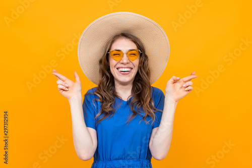 Foto portrait of a girl with crossed fingers, a brunette makes a wish on a yellow bac
