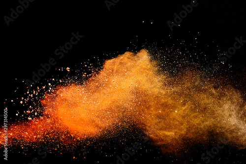 Abstract orange powder explosion isolated on black background. - 297314500
