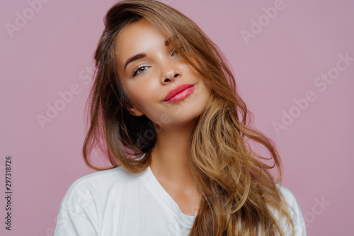 Valokuva  Portrait of satisfied relaxed young female model tilts head, has makeup, fair hair, dressed in white clothes, poses against purple background, has well cared complexion